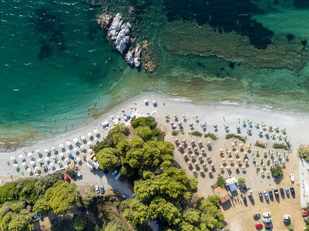 Abstand zwischen Sonnenschirmen am Strand Milia auf Skopelos. Luftbild im Sommer 2021