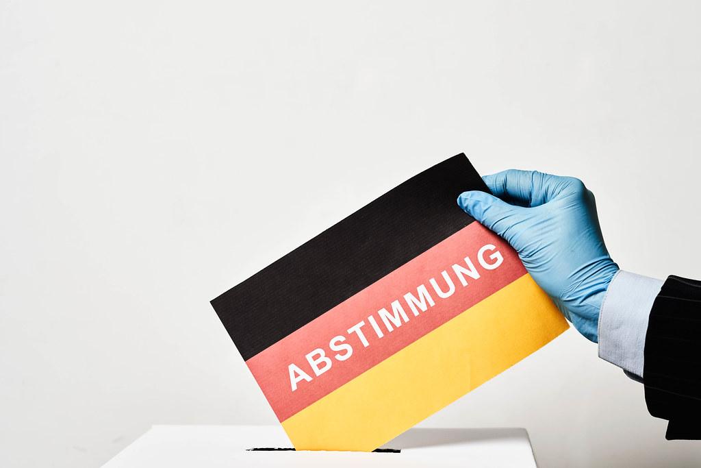Abstimmung für den Bundestag in Corona-Zeit: Hand eines Wählers mit Einmalhandschuh bei der Wahlurne