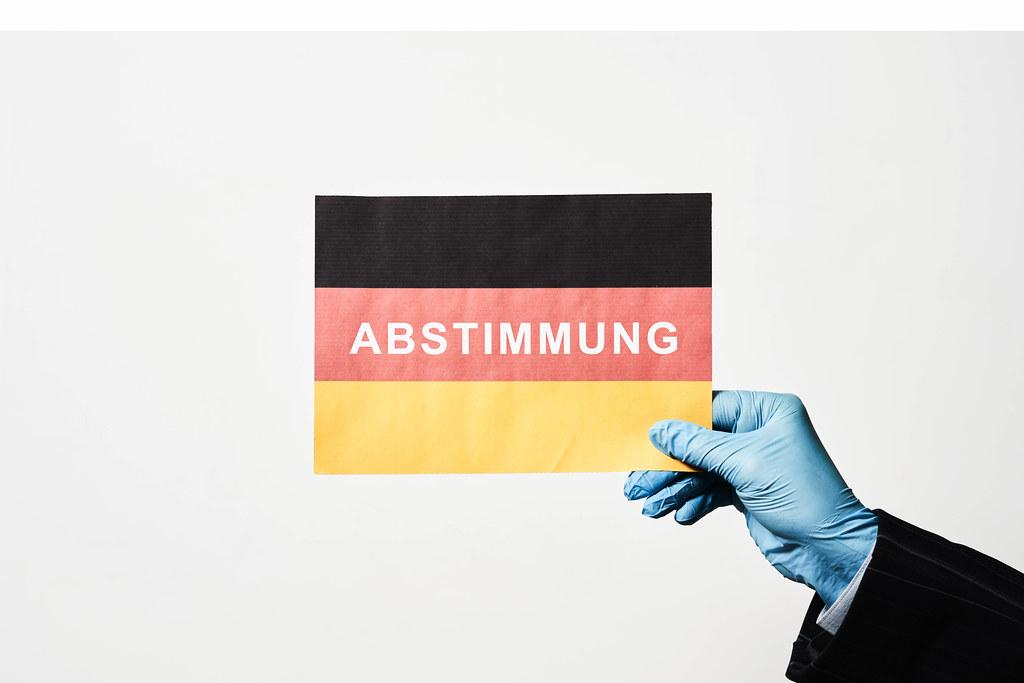 Abstimmung: Schrift auf der deutschen Flagge mit Einmalhandschuh gehalten. Wahl in Corona-Zeit