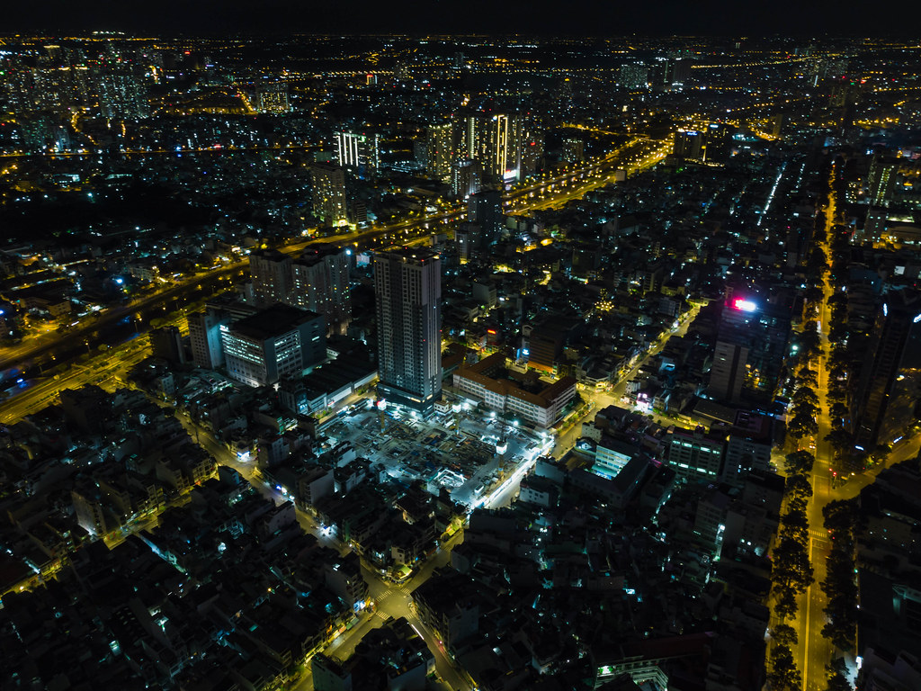 Aerial Drone Night Shot of Ho Chi Minh City, Vietnam with an Apartment Building Construction Site and many Buildings with no Traffic on the Streets