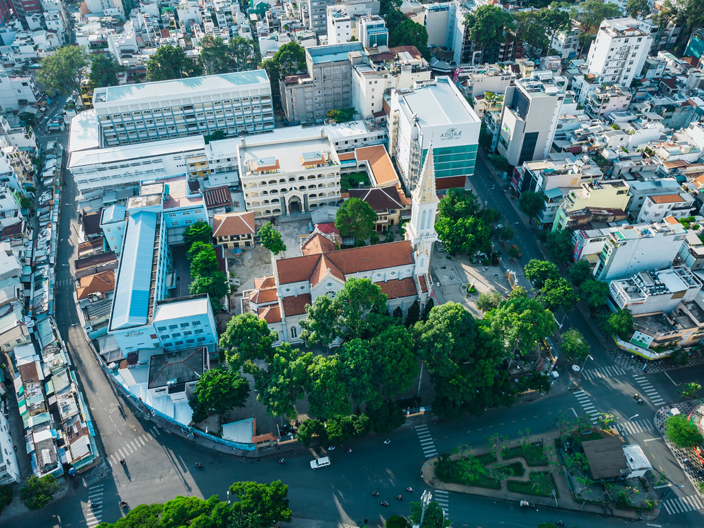 Aerial Drone Photo of  Catholic Huynh Si Church with many Trees and Buildings around it in the City Center of Ho Chi Minh City, Vietnam