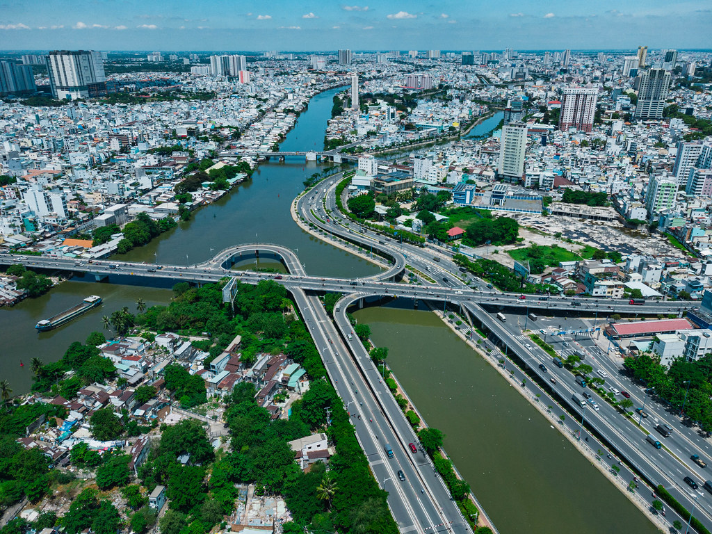 Aerial Drone Photo of Creative Bridge System over Saigon River with many Buildings and different Districts in the Background in Ho Chi Minh City, Vietnam