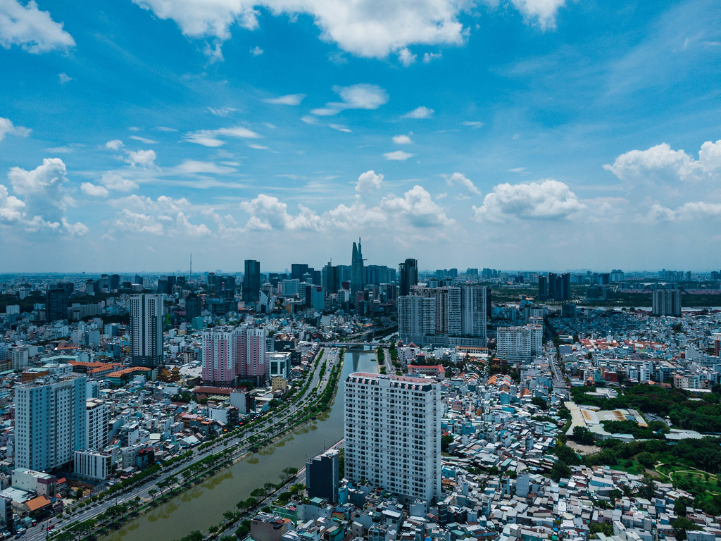Aerial Drone Photo of Ho Chi Minh City, Vietnam with many Apartment Buildings, Bitexco Financial Tower in District 1, Saigon River, Landmark 81 on a Cloudy Day