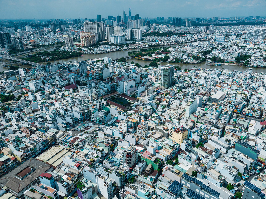 Aerial Drone Photo of many Buildings and Houses in different Districts in front of the Skyline with Skyscrapers of Ho Chi Minh City, Vietnam