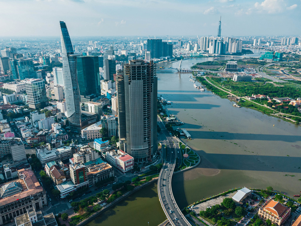 Aerial Drone Photo of the City Center in District 1 with Bitexco Financial Tower with Heli Pad, Bridge Construction over Saigon River and Landmark 81 Tower in the Background in Ho Chi Minh City, Vietnam