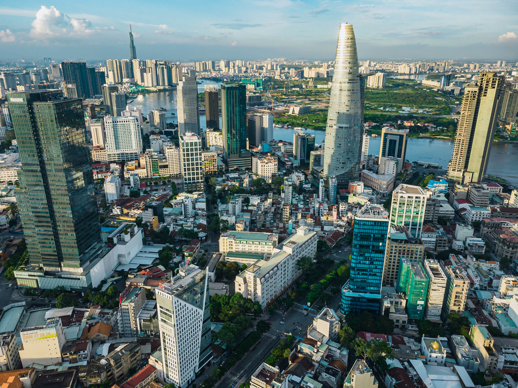 Aerial Drone Photo of the City Center of Ho Chi Minh City, Vietnam with Bitexco Financial Tower and Offices and Lanmark 81 and Saigon River in the Background
