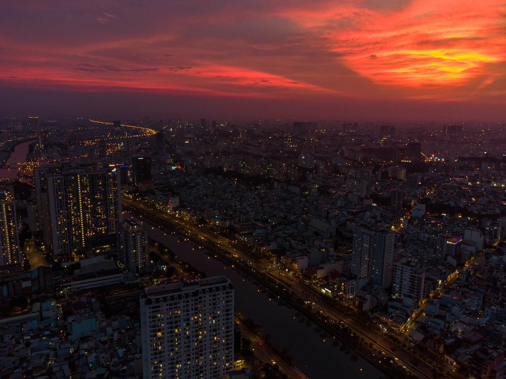 Aerial Drone Photo with Red Sunset Sky,  Buildings and Traffic Lights around Saigon River of Ho Chi Minh City, Vietnam