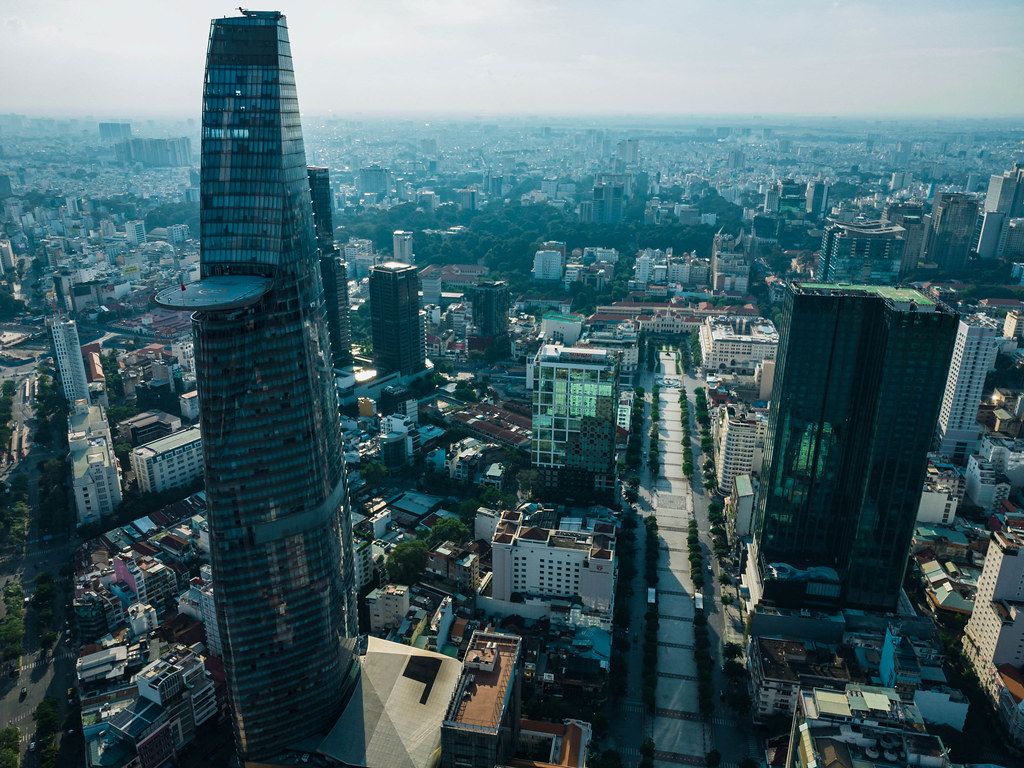 Aerial Drone Shot of Bitexco Financial Tower with Helicopter Pad, empty Nguyen Hue Walking Street and the famous Ben Thanh Market in the Background in Ho Chi Minh City, Vietnam