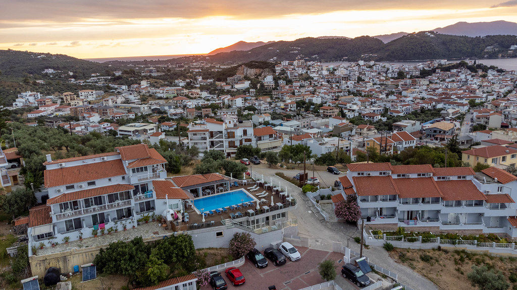 Aerial image of the Greek island of Skiathos with hotels and swimming pool in the foreground