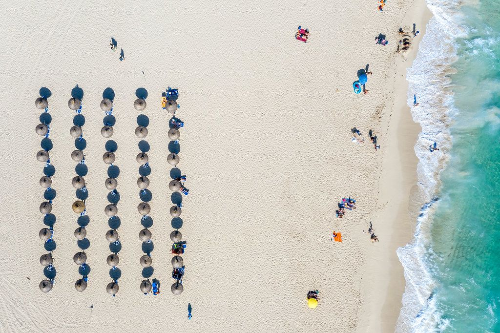 Aerial photo: Five rows of parasols cast their shadows on the sand. Cala Mesquida, Mallorca
