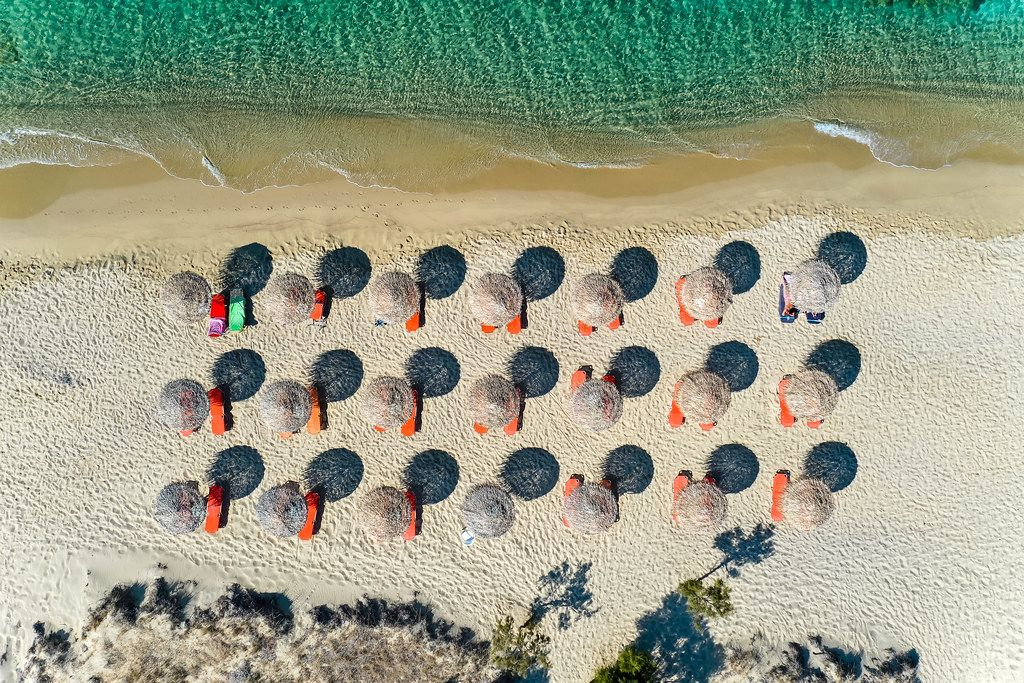 Aerial photo: geometry on Plaka beach on Naxos. Three rows of straw parasols, dunes and sea