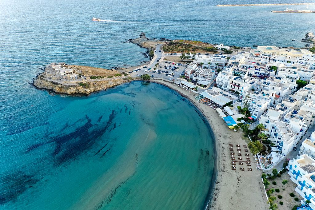 Aerial photo of the Agios Georgios beach, the blue waters and the blue-white buildings of Naxos City