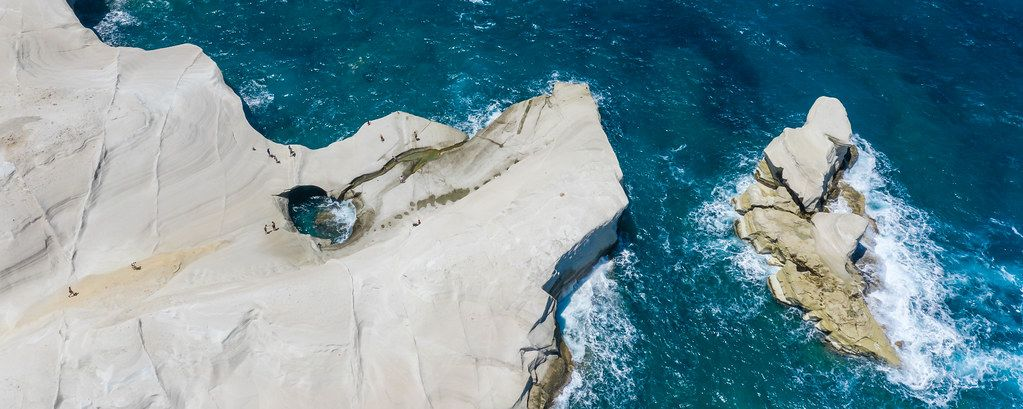 Aerial photo of the white cliffs of Sarakiniko in Milos, with a hole shaped by the waves