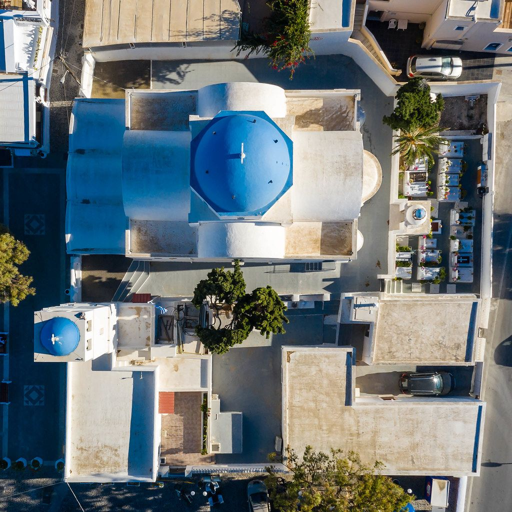 Aerial photo of typical Greek church and bell tower with blue domes and small cemetery