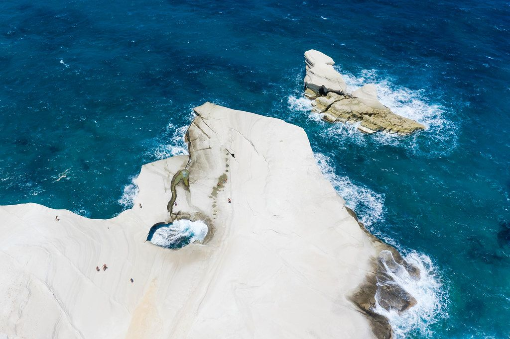 Aerial pic of rock formations in Sarakiniko, Milos. Hole in the cliff, created by strong winds and waves