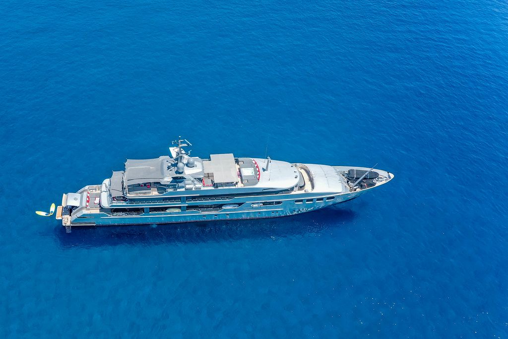 Aerial picture of a mega yacht in the blue waters of the south Aegean off the coast of Milos, Greece