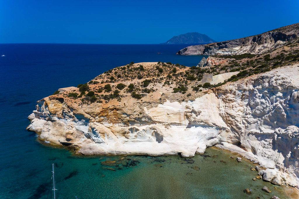 Aerial shot: spectacular cliffs by the beach of Agios Ioannis on the southwest coast of Milos, Greece