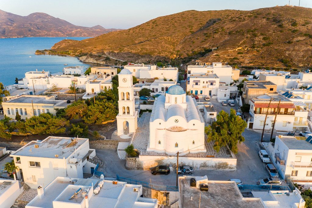 Aerial view of Adamantas, Milos, Greece with white church and bell tower with the typical blue domes