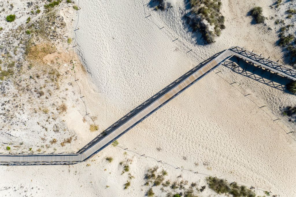 Aerial view of long wooden pathway on the sand across the beach of Cala Mesquida, Mallorca