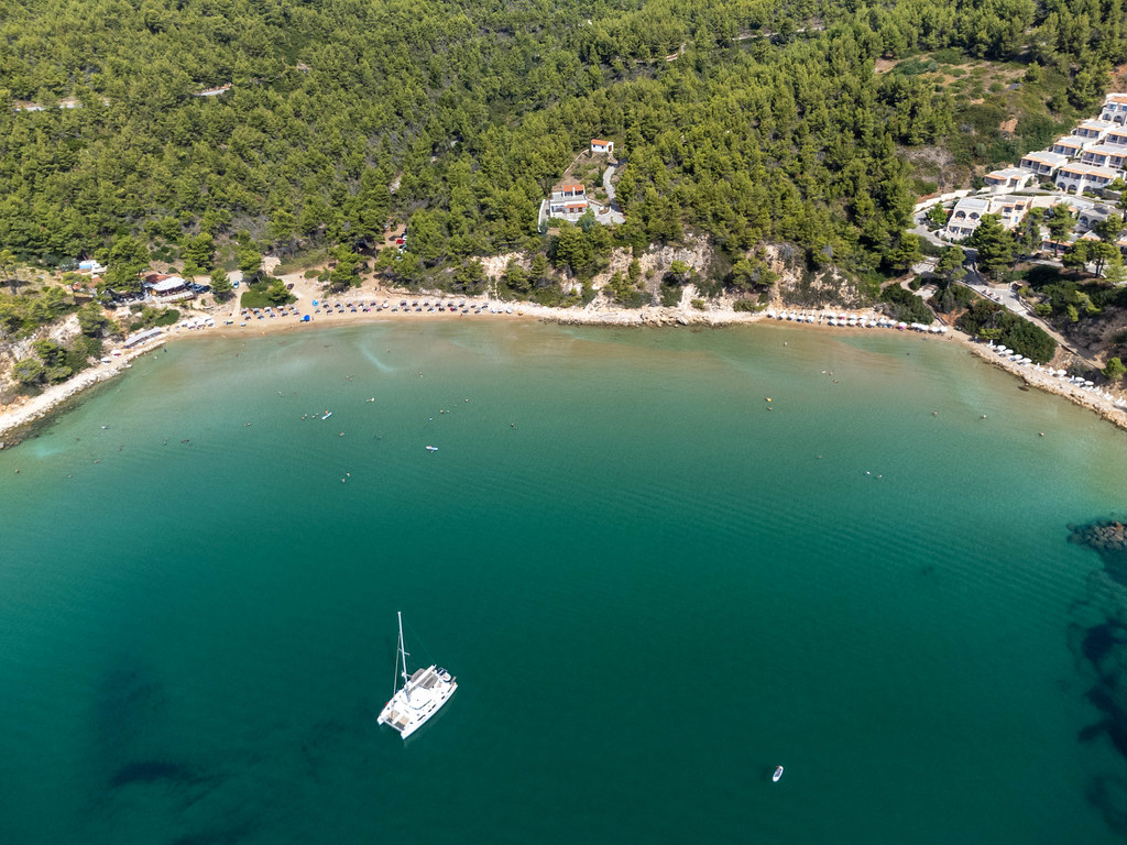 Aerial view of the beach and bay of Chrisi Milia with a catamaran in the turquoise sea