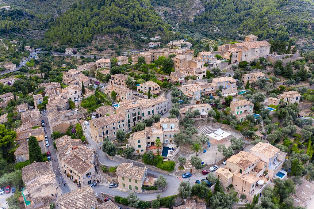 Aerial view of the houses of Deià immersed in the green. Artist village on the west coast of Mallorca