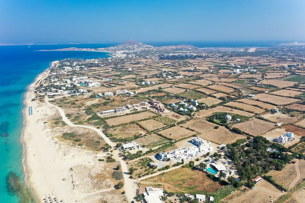 Aerial view of the island of Naxos, Greece with flat farmland, beach and stunning transparent waters