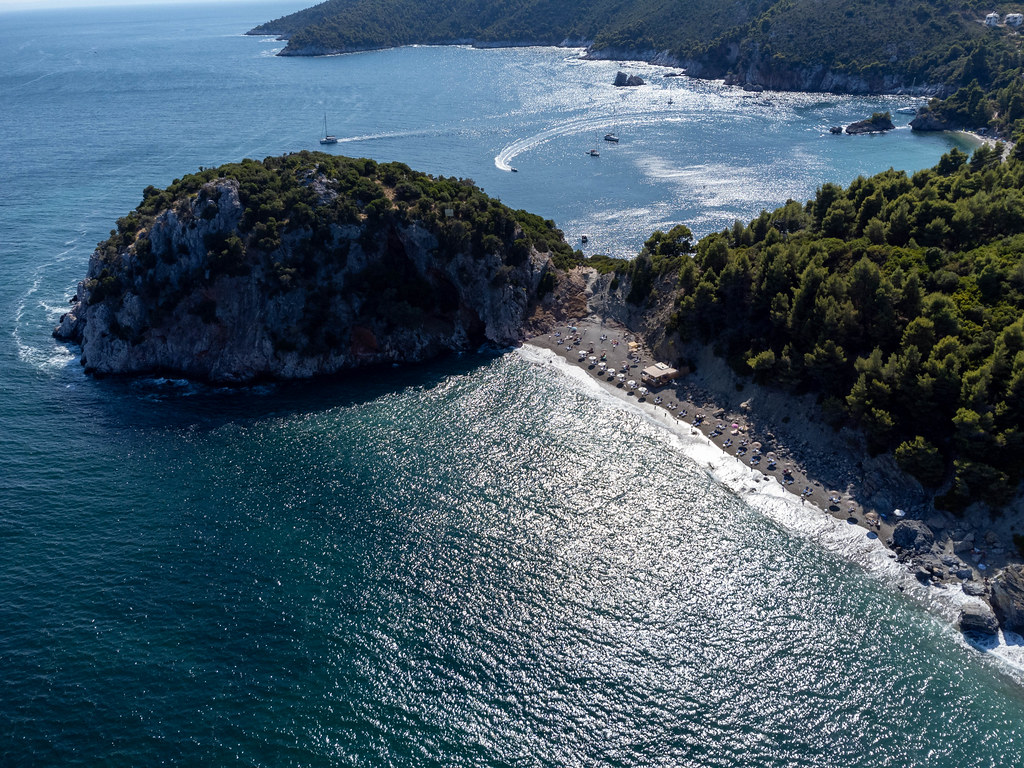 Aerial view of Velanio beach with silver sand and rocky headland on the Greek island of Skopelos