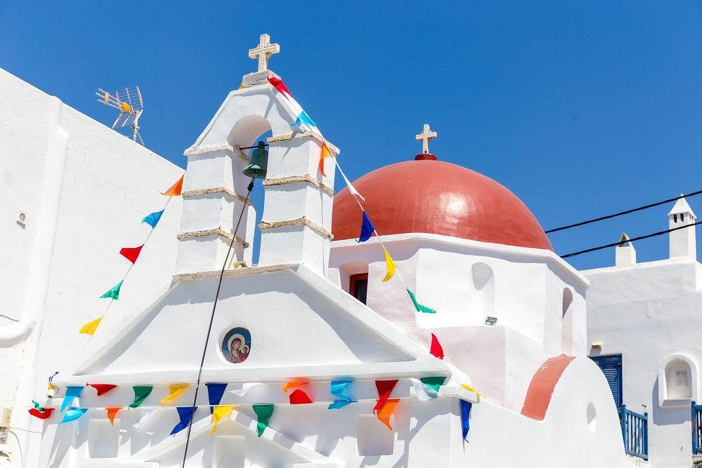 Agia Anna, Mykonos: weiße Kirche mit roter Kuppel und Girlande zum Gedenktag der Heiligen Anna