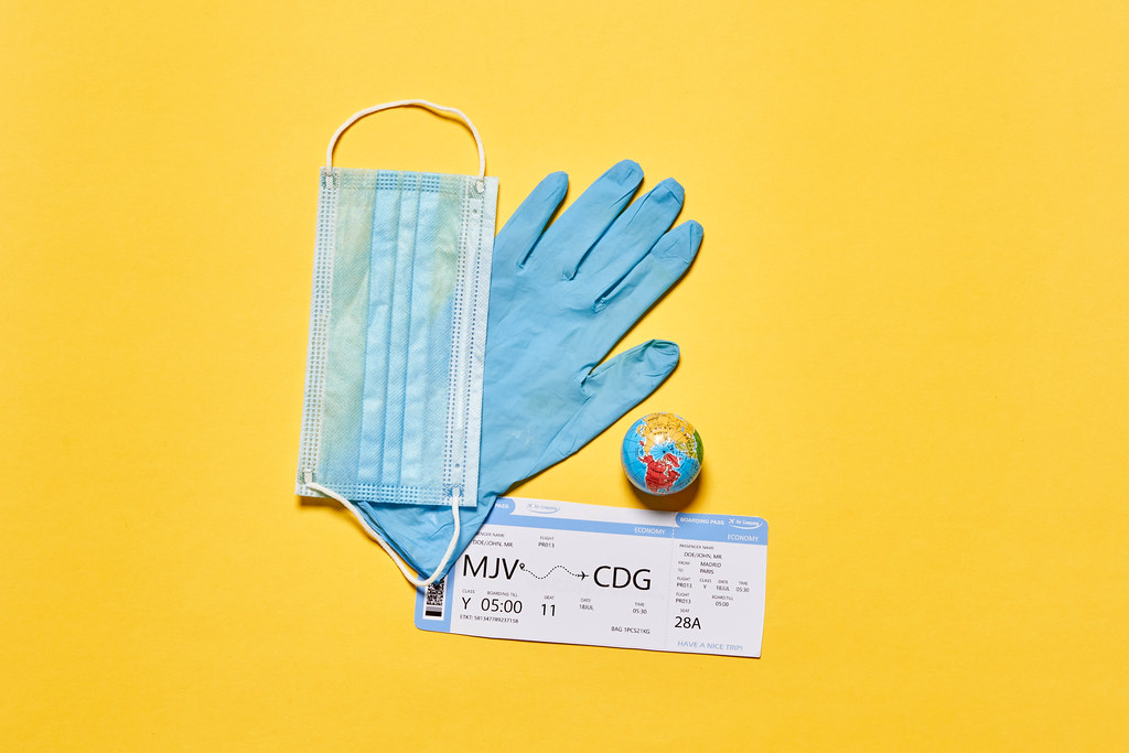 Air ticker, face mask, medical glove and miniature globe - as a symbol of new normal in the travel industry