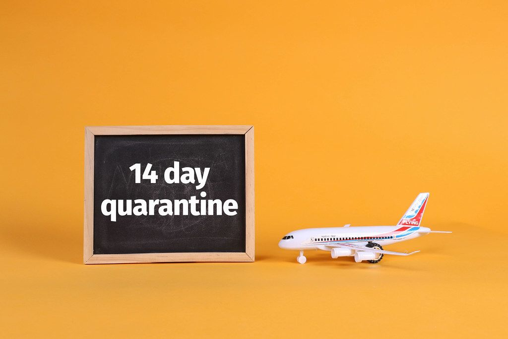 Airplane and blackboard with 14 day quarantine text