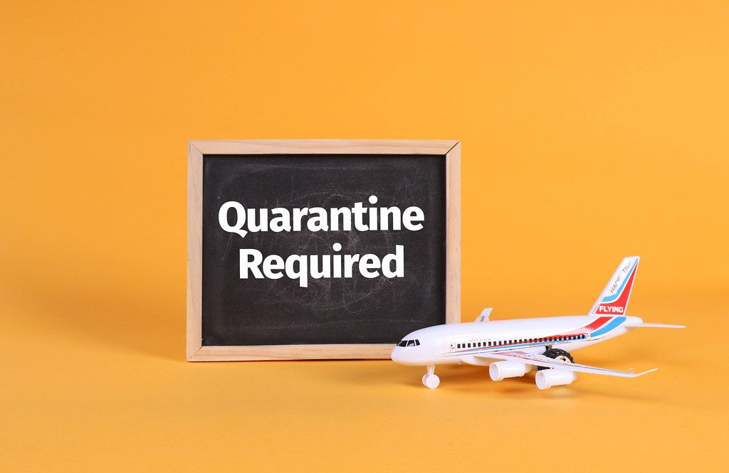 Airplane and blackboard with Quarantine Required text