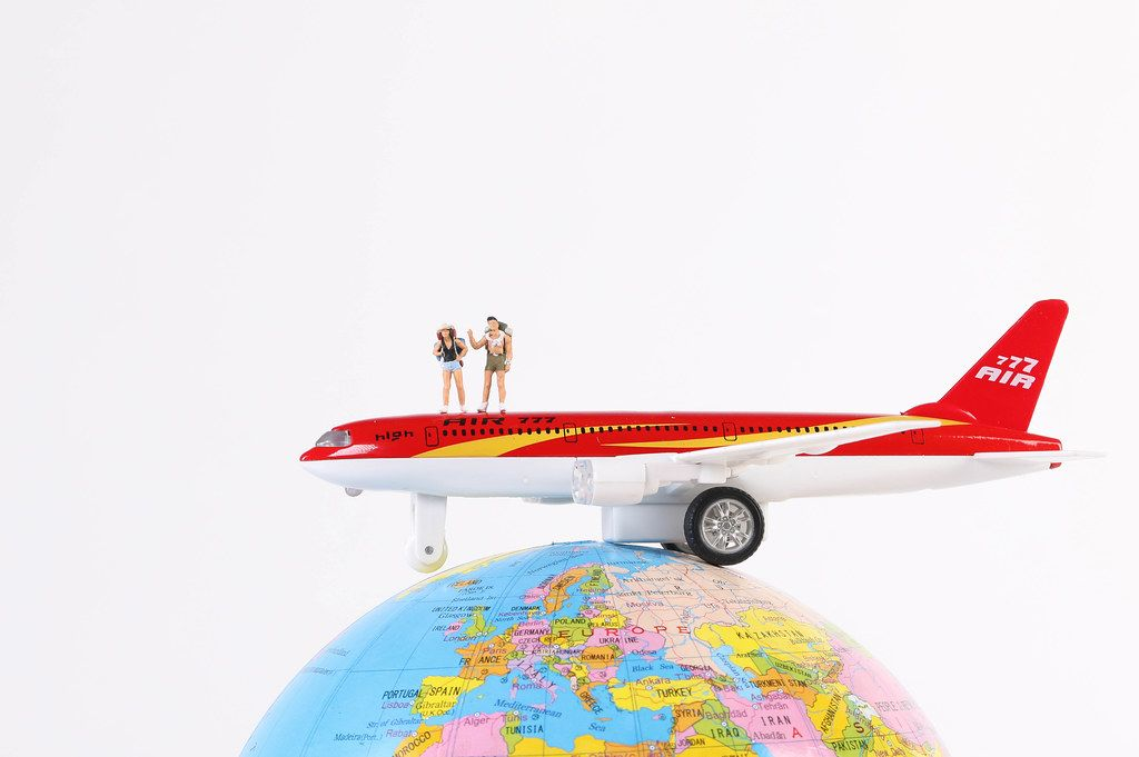Airplane with miniature travelers on globe