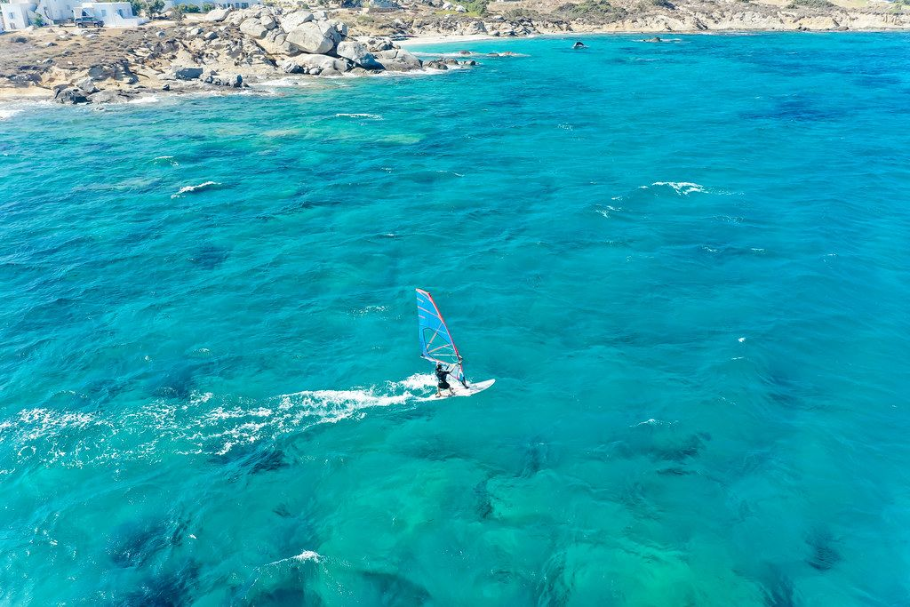 Aktiver Urlaub: ein Windsurfer vor der Küste bei Mikri Vigla auf Naxos, Griechenland. Luftaufnahme