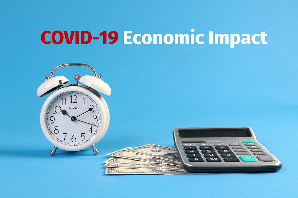 Alarm clock, calculator and money with COVID-19 Economic Impact text