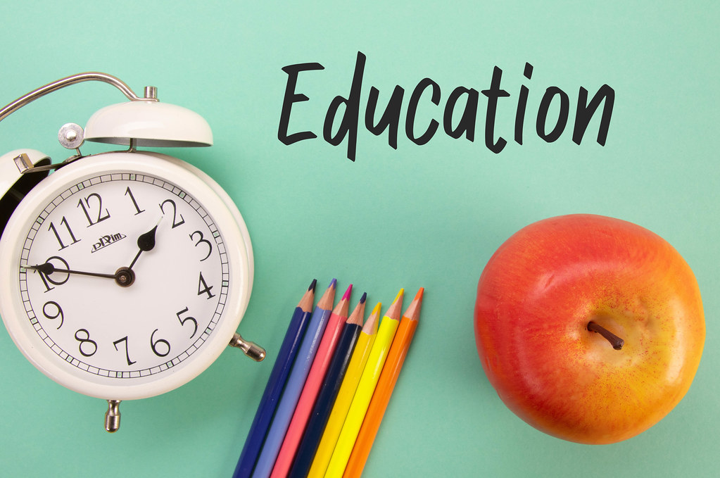 Alarm clock, colored pencils and apple with Education text