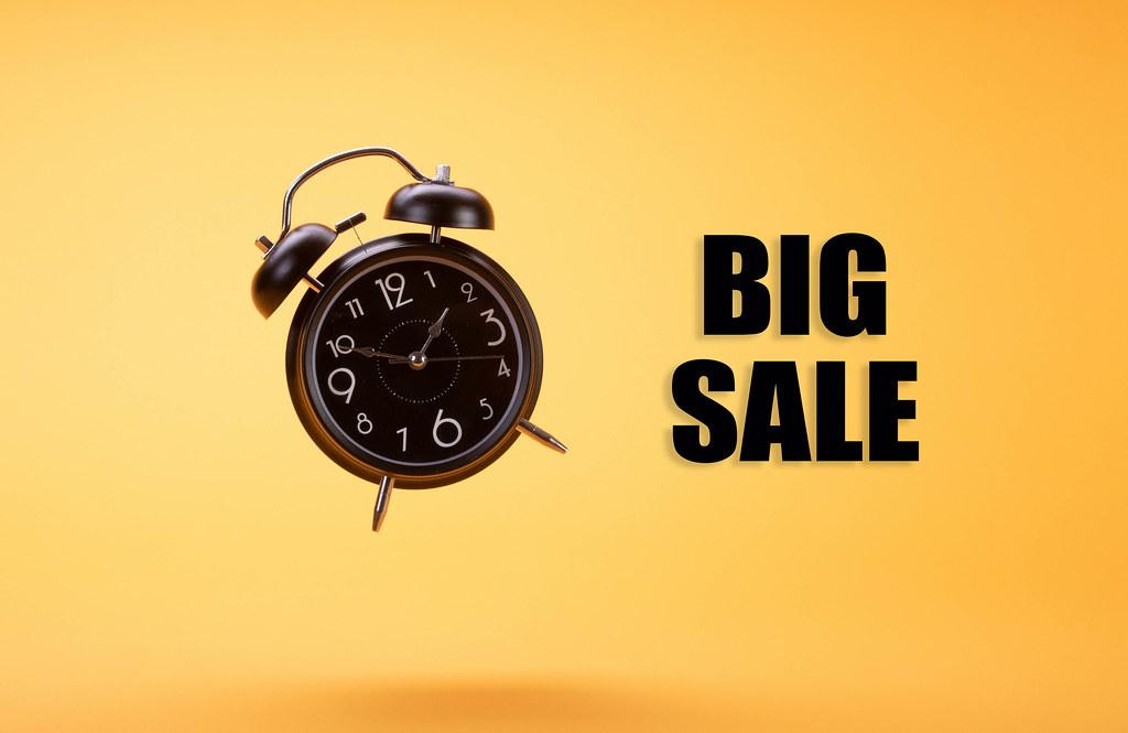 Alarm clock with Big Sale text on orange background