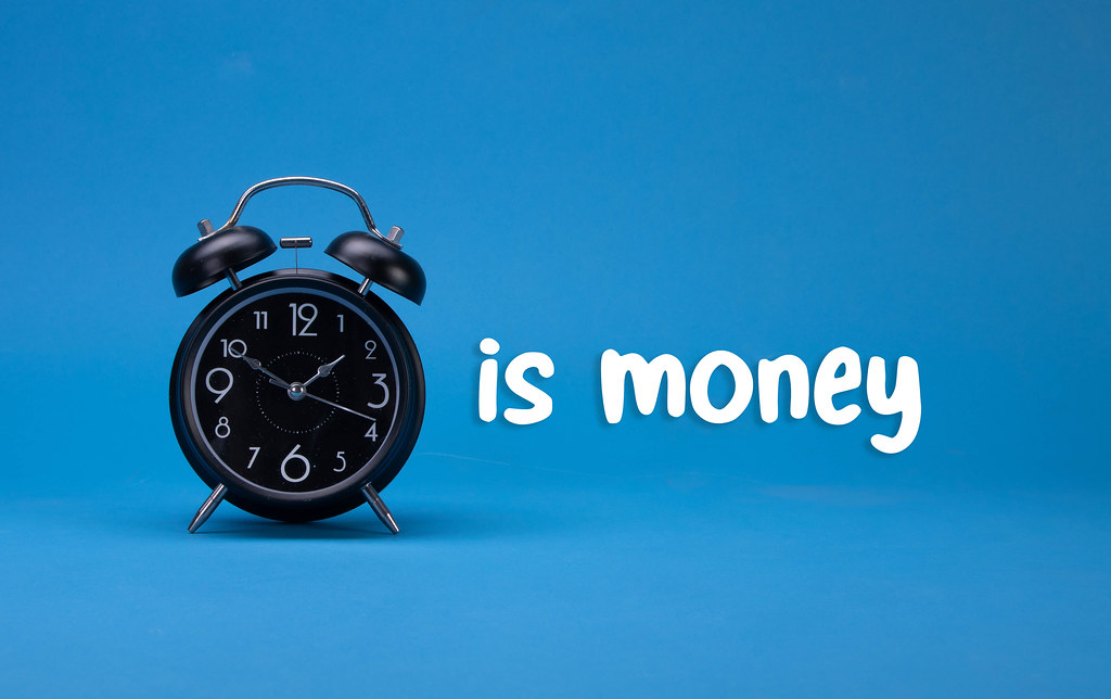 Alarm clock with Time is money text on blue background