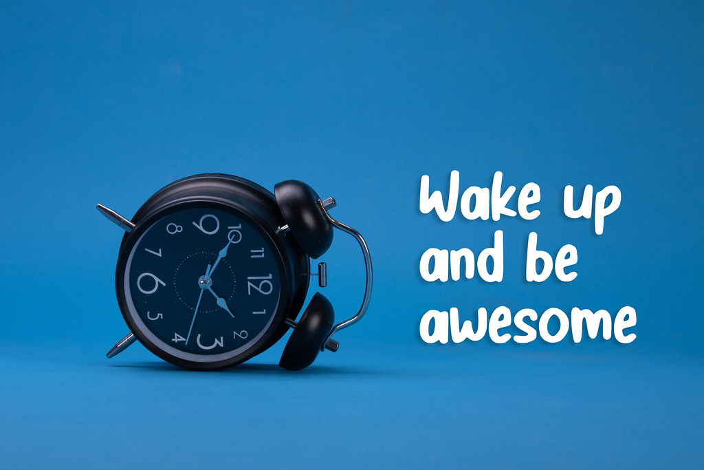 Alarm clock with Wake up and be awesome text on blue background
