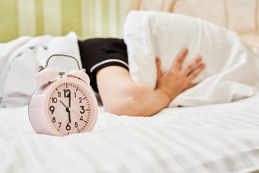 Alarming clock and woman covering head with pillow while trying to sleep in bed