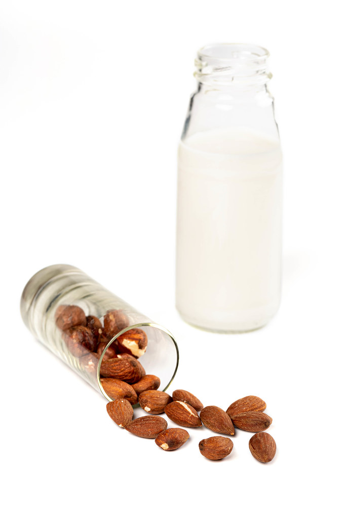 Almond milk in glass bottle with almond nuts on white. Vegetarian eating