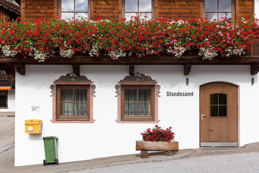 Alpine architecture: wooden door and windows, balcony with many flowers. Alpbach registry office