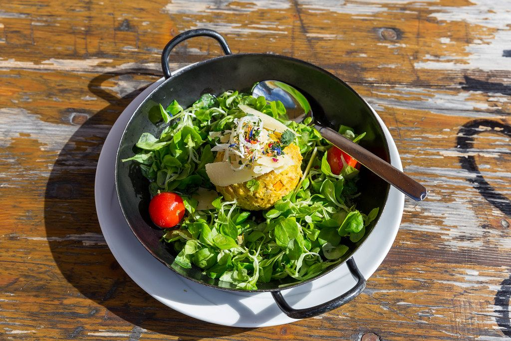 Alpine food in Tyrol, Austria: a pumpkin Knödel served in a pan with green salad and tomatoes