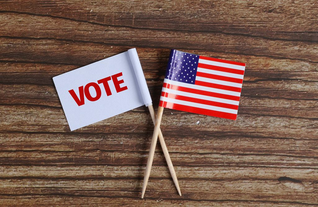 American flag and white flag with vote text on wooden table