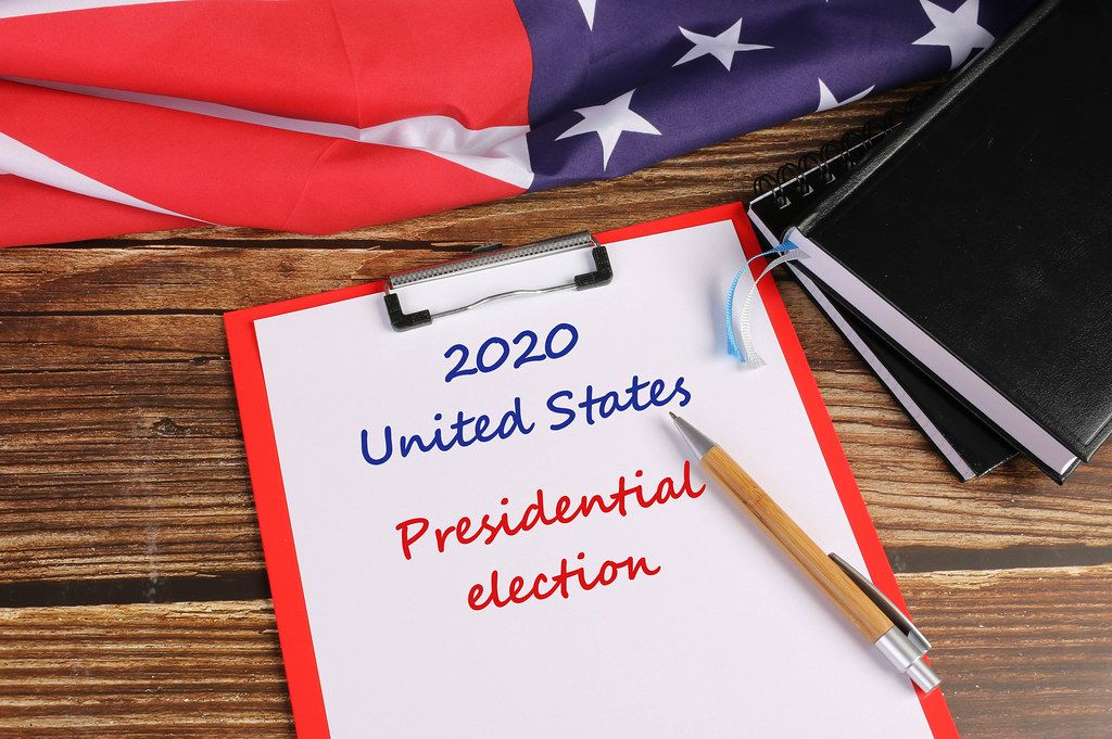 American flag on wooden table with 2020 United States Presidential election text