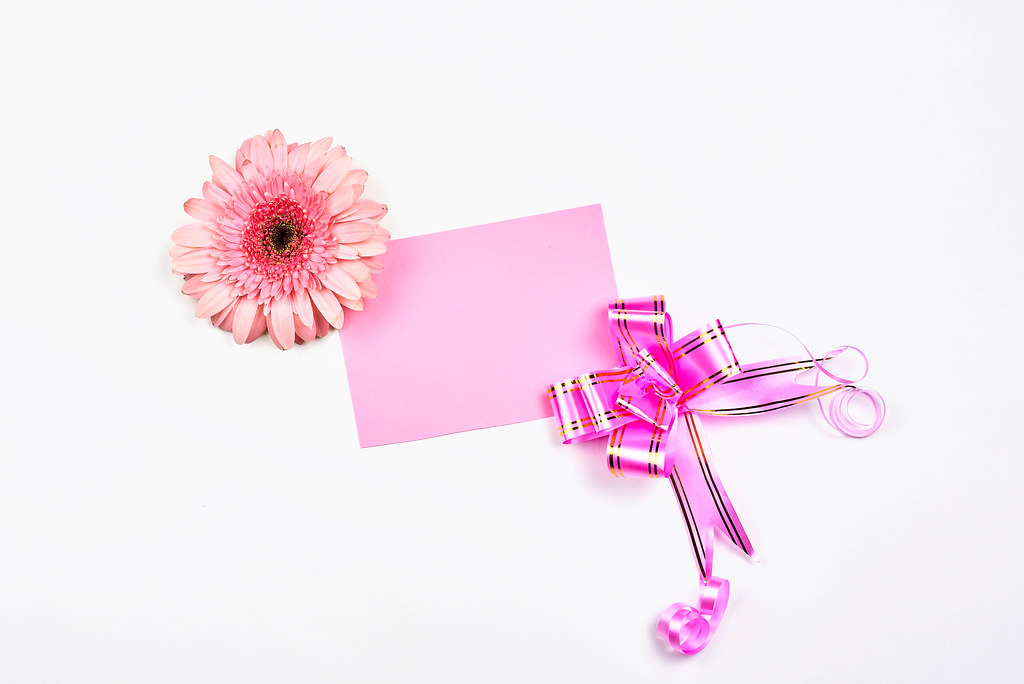 An empty greeting card decorated with ribbon and flower