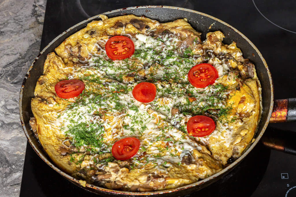 An omelet with mushrooms, cheese, tomatoes and herbs is fried in a frying pan
