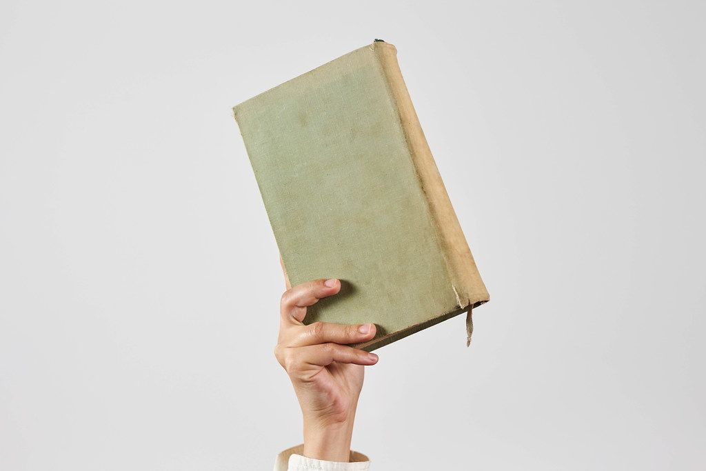 An unrecognizable woman holds an old book. Online library or reading literature online concepts