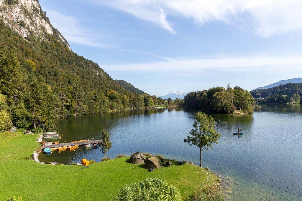 Angeln am Reintalersee in Tirol: Zelte und Campingstühle am Ufer, Angler auf Holzbooten