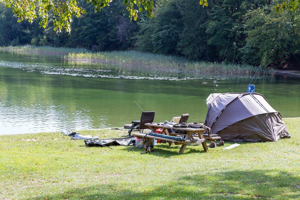Angeln am Reintalersee: Zelt und Campingstühle neben Holzbänken und Tisch mit Angelausrüstung