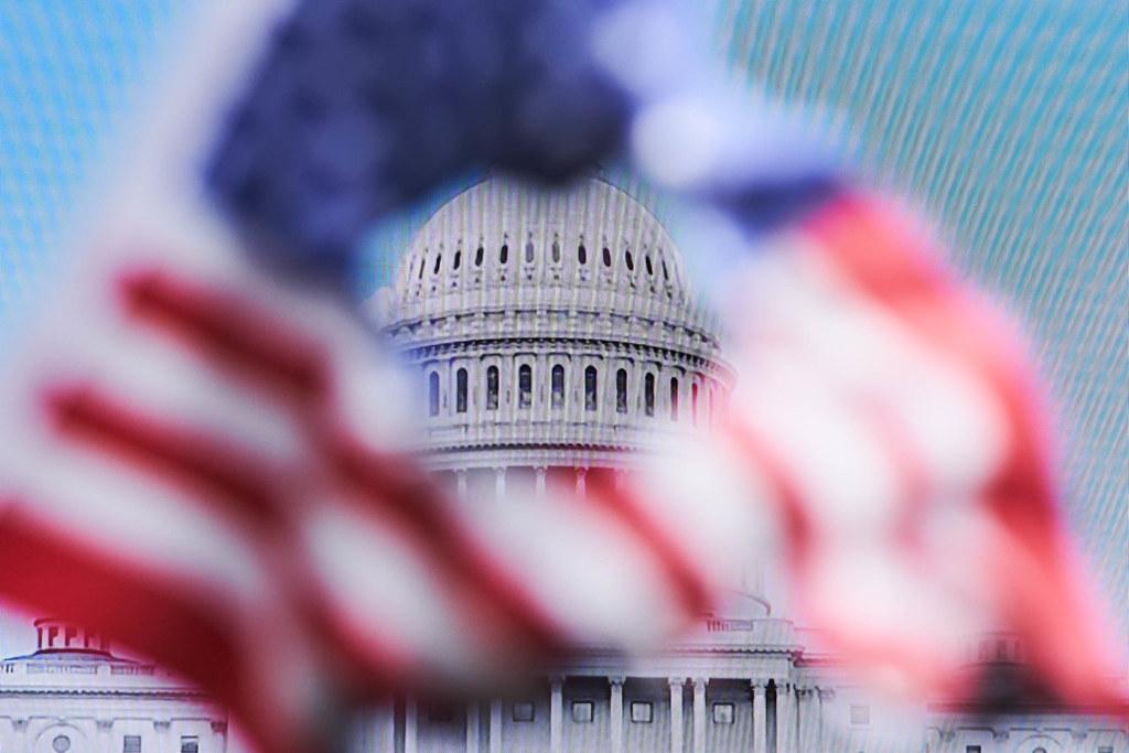 Angriff auf US-Kapitol: USA-Flagge mit Loch in der Mitte vor Fernseher, der das Kapitol zeigt